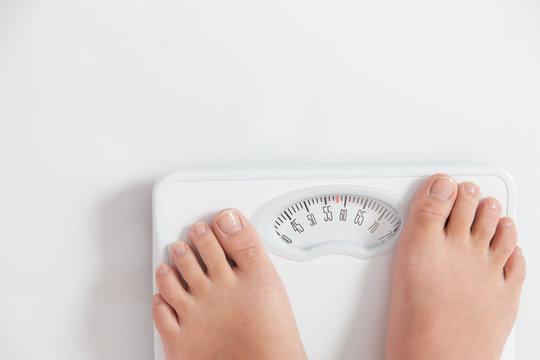体重を測る女性(58kg)・白バック