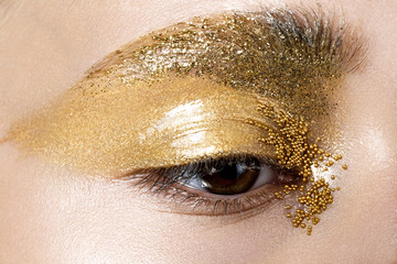 Closeup image of beautiful woman eye with gold makeup