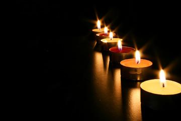 Teelichter auf schwarzem Hintergrund verbreiten warmes Licht und romantische Atmosphäre