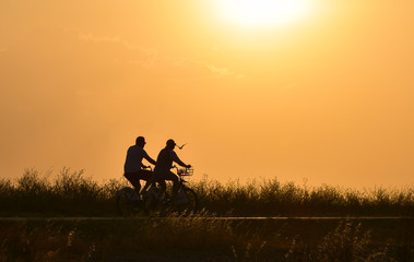Couple riding bicycle on sunset sky, silhouette.