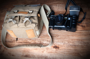 Old camera and bag, wooden background