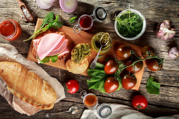 Baguette, ham and vegetables. Appetizers on wooden cutting Board.