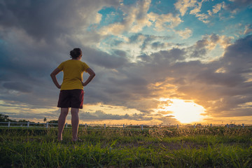 Beautiful woman on green meadow watching the sunset ray light and dramatic clouds in summer