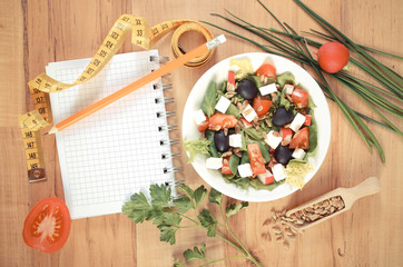 Vintage photo, greek salad with vegetables, centimeter and notepad for notes, healthy nutrition and slimming concept
