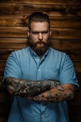 Tatooed  bearded male in a blue shirt.