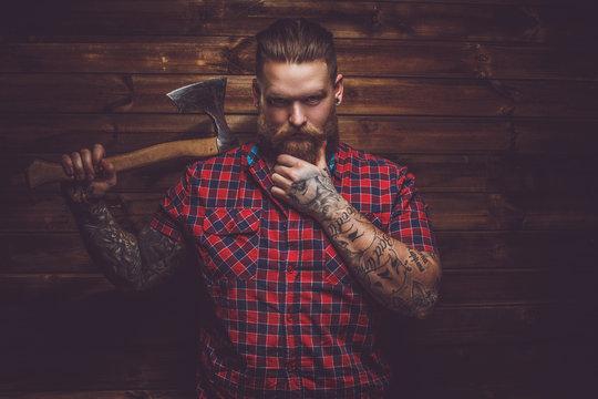 Tatooed  bearded male holding axe.