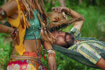close up of boho woman with feathers in hair and her man lying i