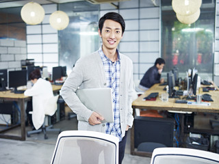 portrait of a young asian entrepreneur standing in office with laptop under arm