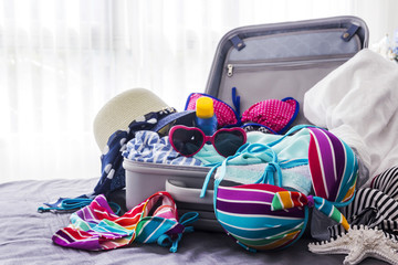 Colorful bikini and clothes in luggage on the bed