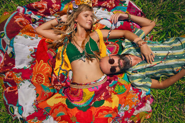 hippie style man and woman lying on green grass