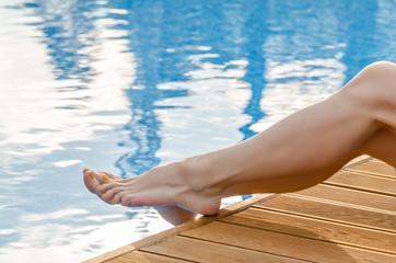 Female legs in the pool water