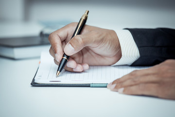 Businessman writing on notebook with pen in the office in blue c