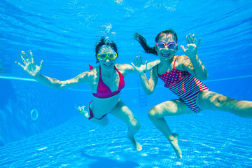 girl with mother playing  underwater
