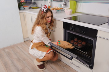 young housewife taking cupcakes from oven