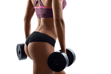 Flawless shape. Cropped studio closeup of perfectly shaped buttocks of a female fitness model posing with dumbbells isolated on white