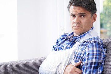 Portrait Of Mature Man With Arm In Sling At Home