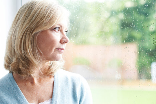 Sad Mature Woman Suffering From Agoraphobia Looking Out Of Windo