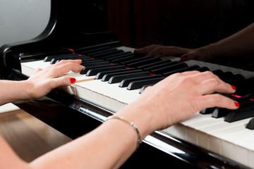 Mani di pianista sulla tastiera del pianoforte durante un'esecuzione