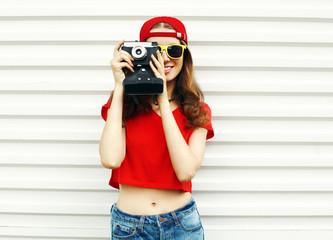 Fashion pretty smiling woman with retro camera over white backgr