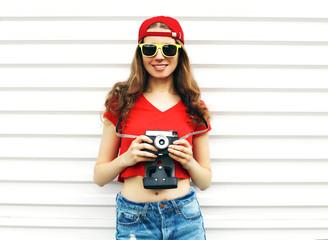 Fashion pretty smiling woman holding retro camera over white bac