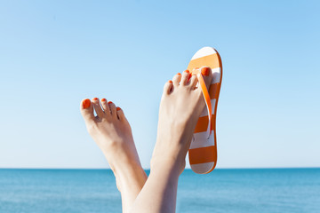 Relaxed woman feet and flip flops on the beach