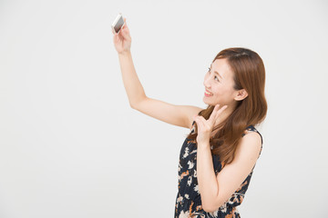 スマートフォンで自撮りする女性