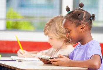 Interracial elementary classroom with students using tablet and