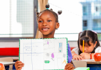 Happy girl at primary school showing her work to the teacher