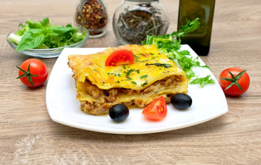 Appetizing lasagna with tomato and olives on a plate.