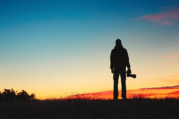 Silhouette of young photographer is enjoying sun. Photographer at the sunrise