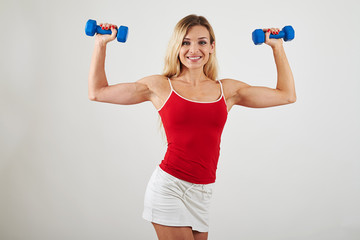 Attractive woman with athletic body holding dumbbells on white