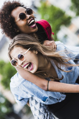 Laughing woman giving her friend a piggyback ride
