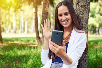 Smiling lady resting under tree and conducting a video call