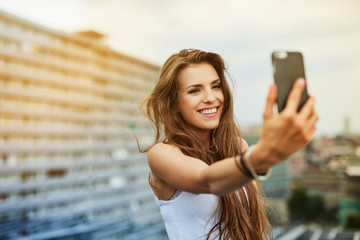 Happy young woman taking selfie on rootfop