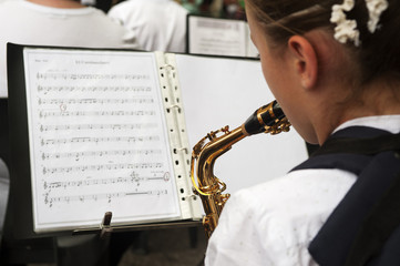 young girl playing a saxophone at a concert