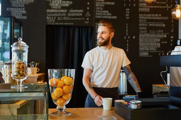 Happy barista, small business owner standing behing the counter