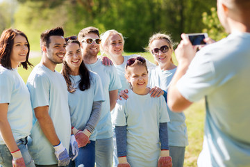 group of volunteers taking picture by smartphone