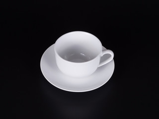 White cup on a saucer isolated on a black background