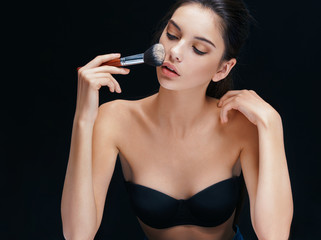 Young brunette applying cosmetic powder on face with brush. Image of girl on black background.