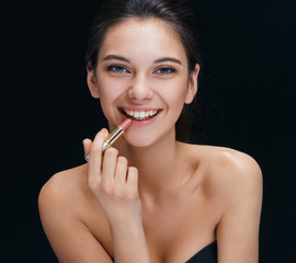 Laughing girl with lipstick. Photo beautiful brunette on black background. Youth and skin care concept