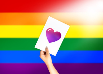 Heart shape on card with hand holding; LGBT color flag backgroun