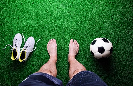 Barefoot football player against green grass, studio shot
