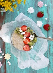 Oatmeal porridge with strawberries and kiwi fruit. Rustic Style