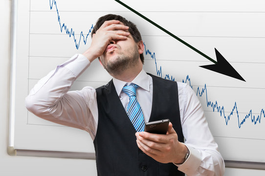 Bad investment or economic crisis concept. Businessman is disappointed from losing in stock exchange. Chart with arrow down on whiteboard in background.