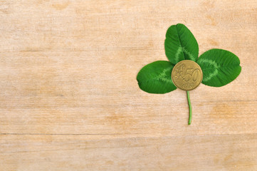 green clover leaf and coin on wooden board (deck)