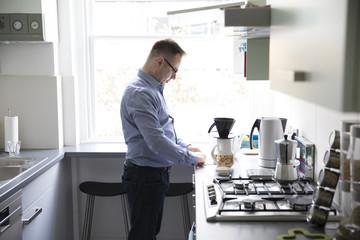 Mature Man Making Fresh Coffee In Kitchen