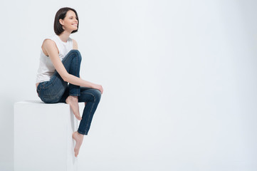 Fototapeta Beautiful young woman sitting on white cube in studio