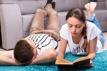 Fasion girl reading book near her boyfriend