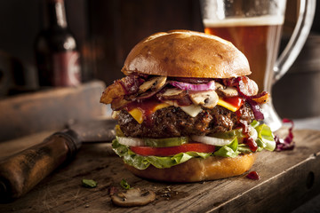 Large cheeseburger on bar with beer