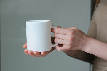 White cup in hand of a girl